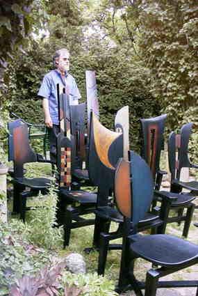 Rudi Muth mit einigen seiner Sitzobjekte im Garten